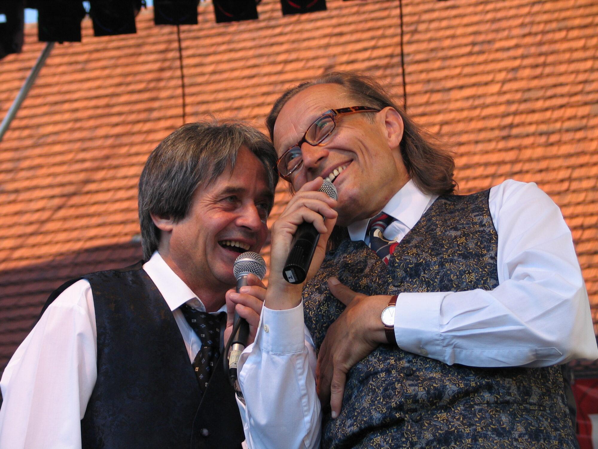 Zdjęcie przedstawia uśmiechniętych Ecika i Masztalskiego podczas występu przed publicznością