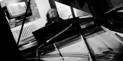 Zdjęcie przedstawia Józefa Skrzeka grającego na fortepianie