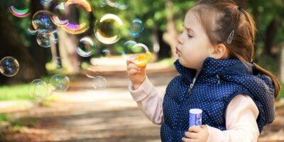Zdjecie przedstawia dziewczynkę w niebieskim kropkowanym bezrękawniku i białej bluzeczce dmuchającą bańki mydlane na tle parkowej alejki.