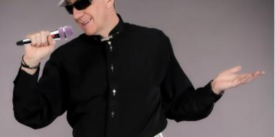 Artysta (Adi) ubrany w biały kapelusz z czarną lamówką, czarną koszulę, białe spodnie, śpiewający do mikrofonu znajdującego się w prawej dłoni artysty. Na nosie czarne okulary.