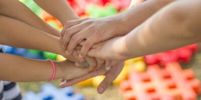 Splecione dłonie dzieci a w tle kolorowe klocki