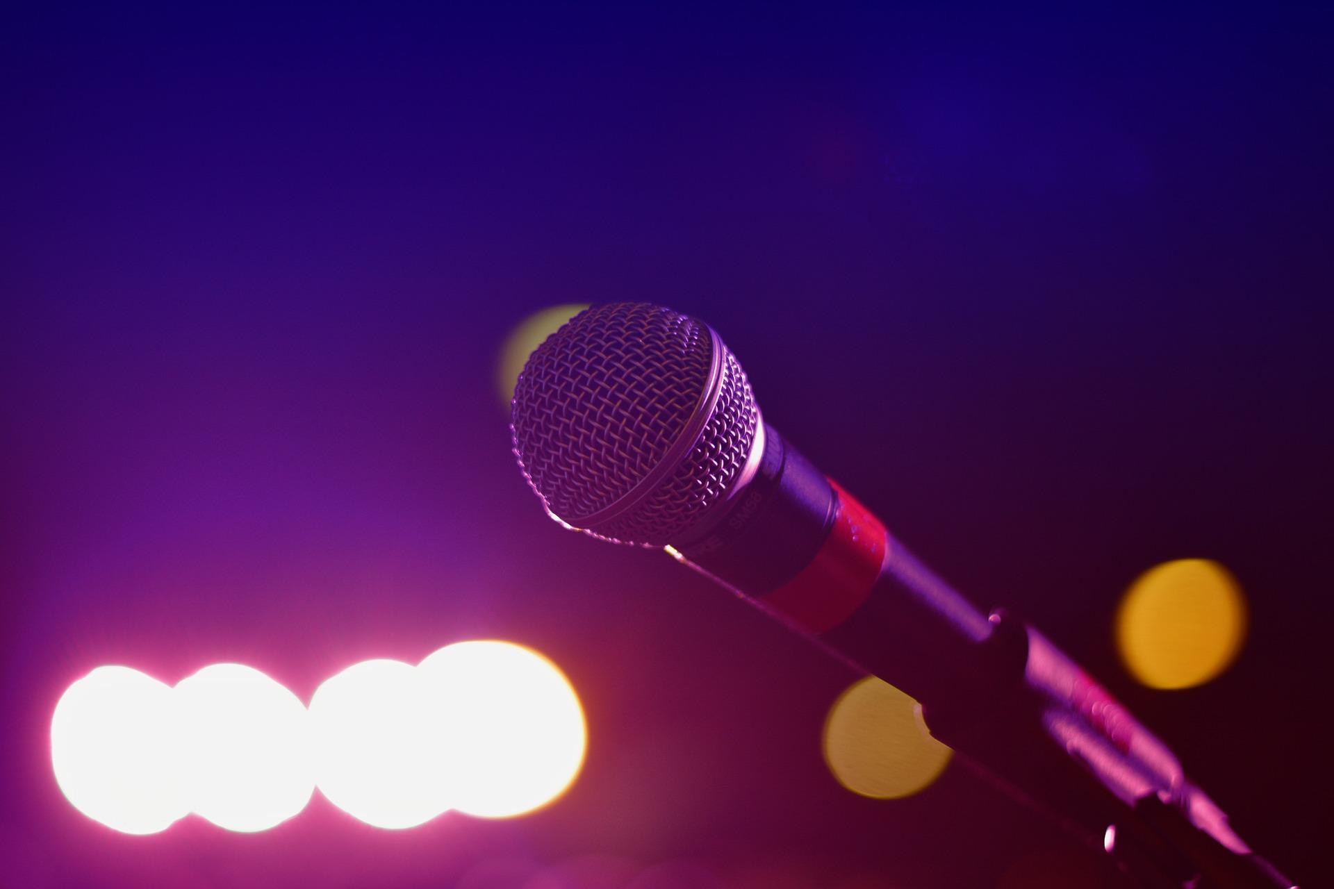 Zdjęcie przedstawia mikrofon, w tle światła estradowe