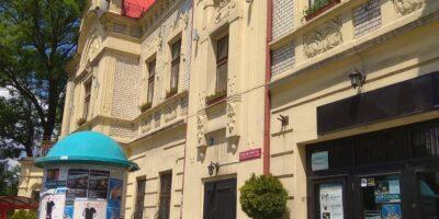 Kremowa fasada budynku SCK-Bytków, a przed nią słup ogłoszeniowy z plakatami reklamującymi wydarzenia