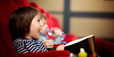 Uśmiechnięte dziecko siedzące na czerwonym fotelu w sali kinowej. W rękach trzyma kubełek z popcornem.