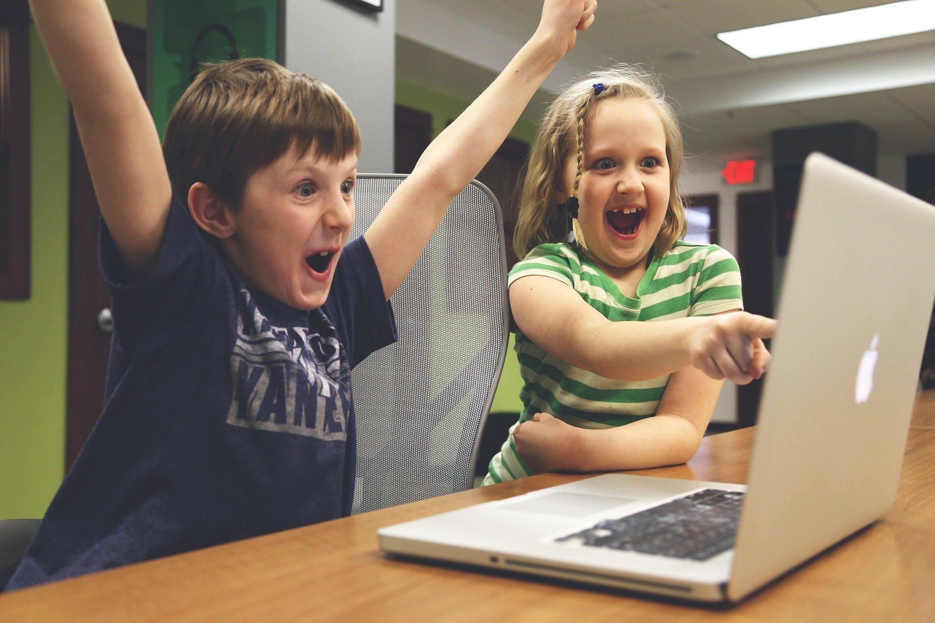 Dwoje dzieci: chłopeic i dzewczynka siedzą przy laptopie z rękoma w górze