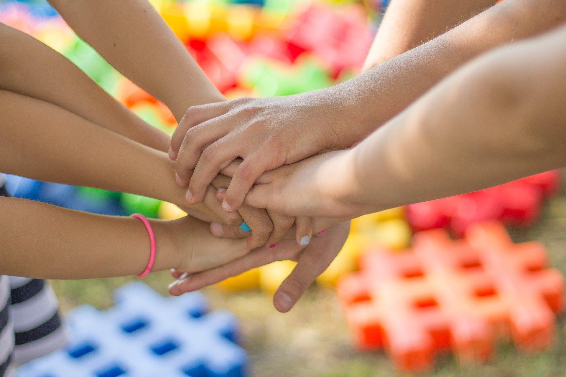 na kolorowym tle trzymające się razem dziecięce rączki