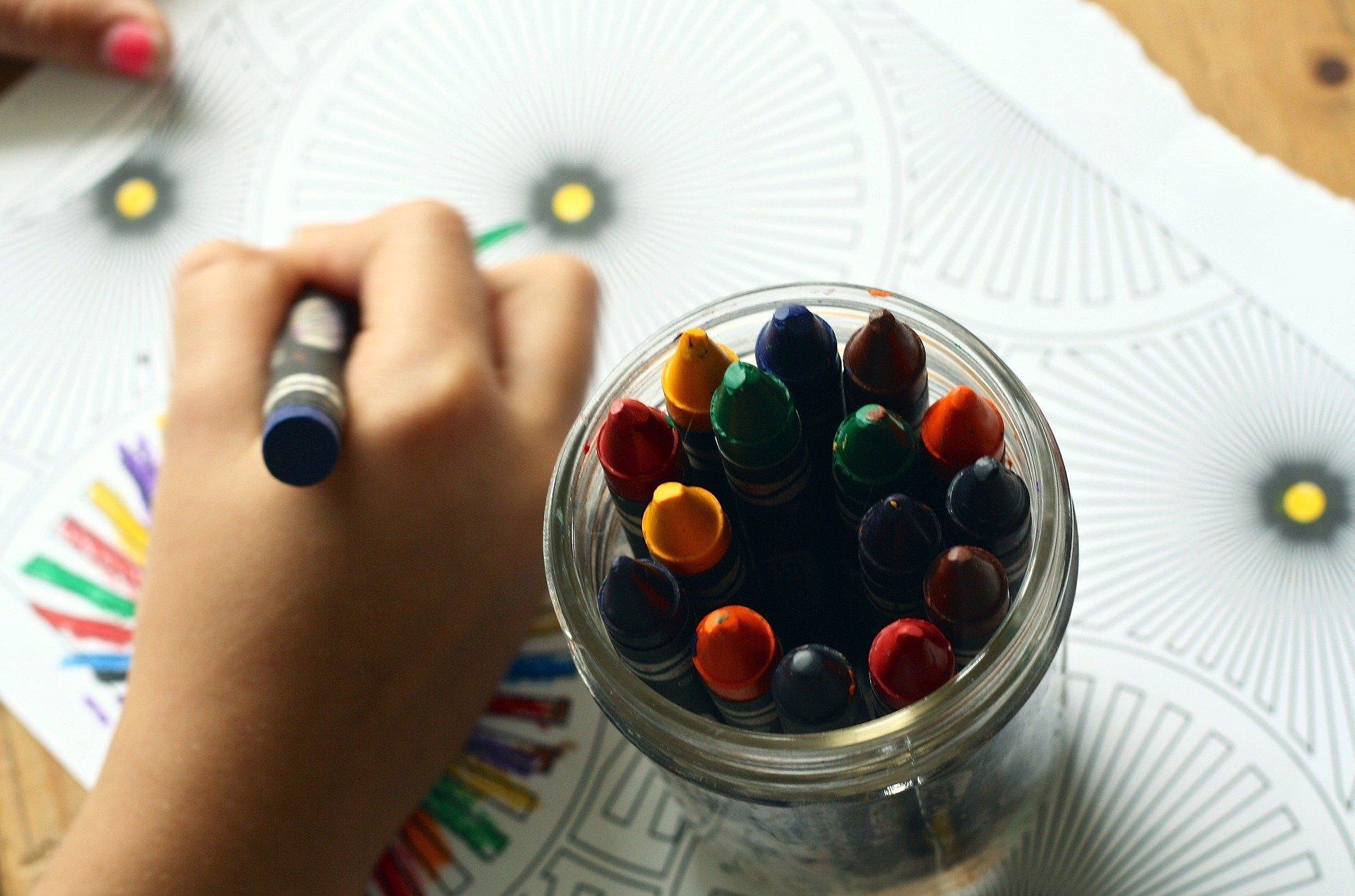 Na zdjęciu kredki świecowe w słoiczku oraz ręka dziecka rysująca nimi