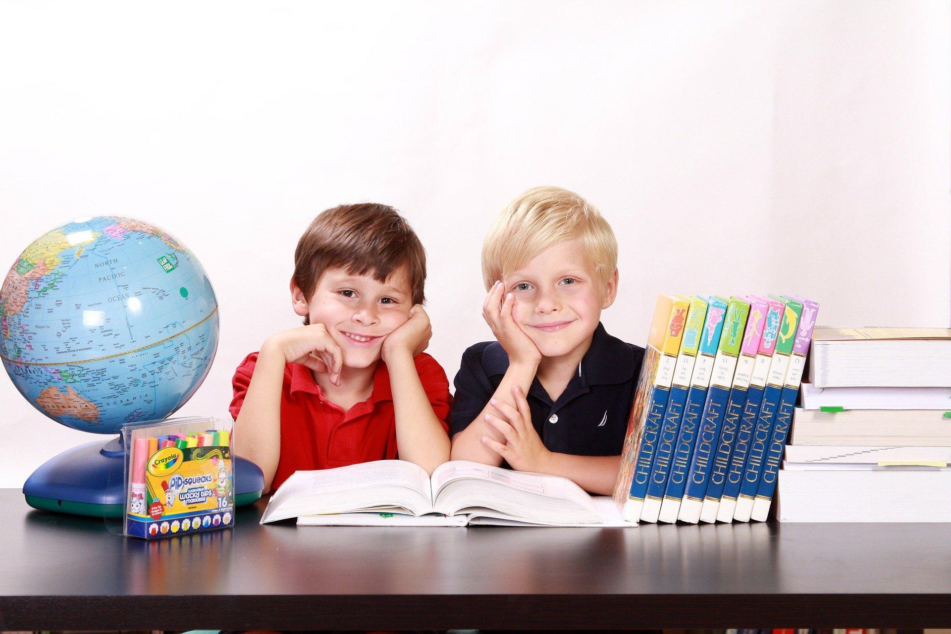 dwóch chłopców przy biurku. Obok stoją globus i książki