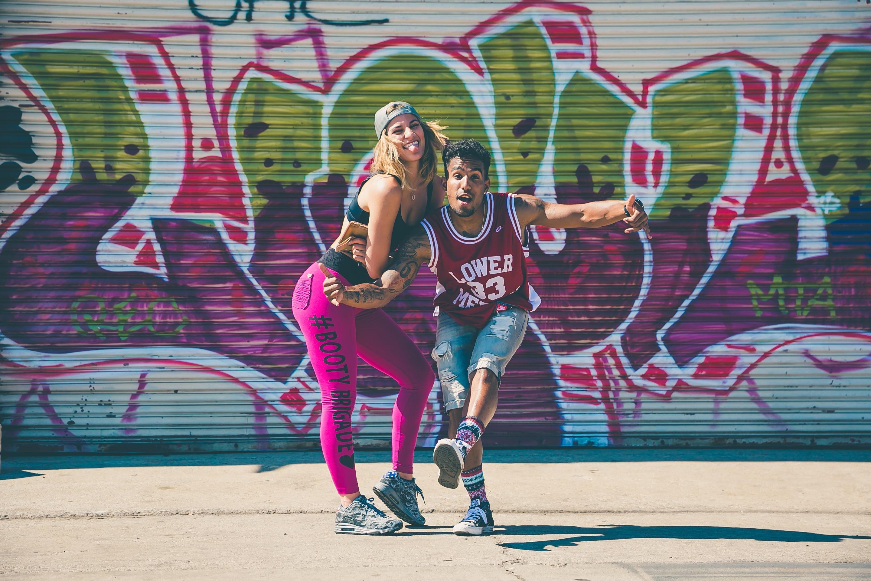 Na zdjęciu dwoje tancerzy hip-hopowych, ubranych w kolorowe stroje, na tle ściany z graffiti