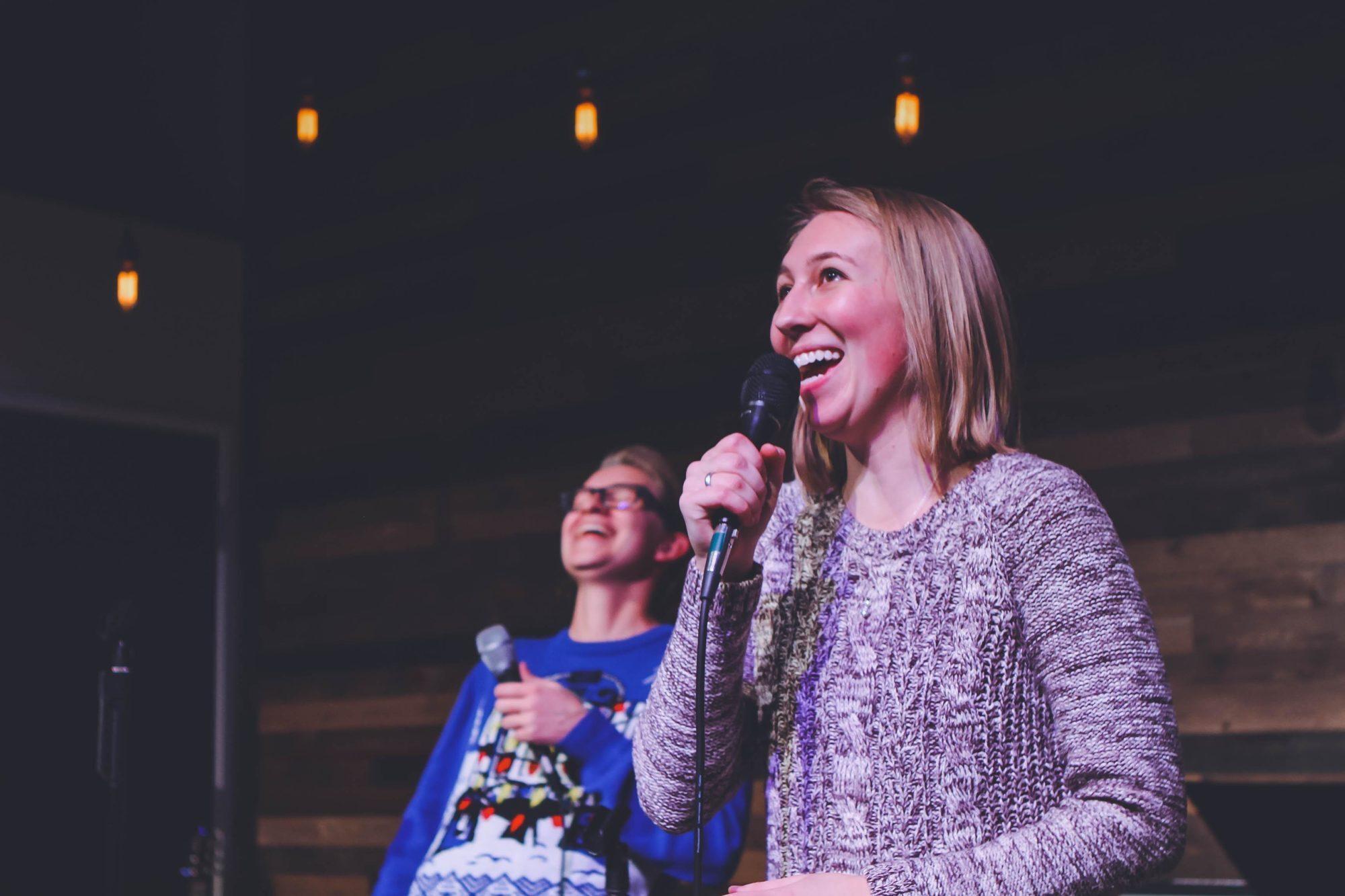 Zdjęcie przedstawia dwie uśmiechnięte osoby trzymające w rękach mikrofony