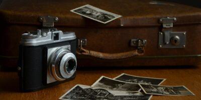 Na zdjęciu aparat fotograficzny, zdjęcia oraz stara, brązowa walizka