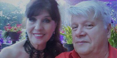 Na pierwszym planie mężczyzna o siwych włosach w czerwonej koszuli. Tuż za nim uśmiechająca się kobieta o ciemnych włosach w czarnej sukience z printami.