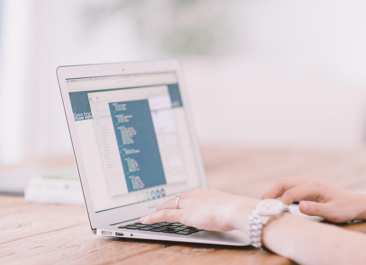 Otwarty laptop oraz ręcę osoby na nim pracującej