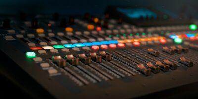 Czarny mikser dźwięku z suwakami i kolorowymi przyciskami.