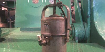 Zabytkowa lampa górnicza typu karbideowego stojąca na tle maszyny górniczej koloru zielonego