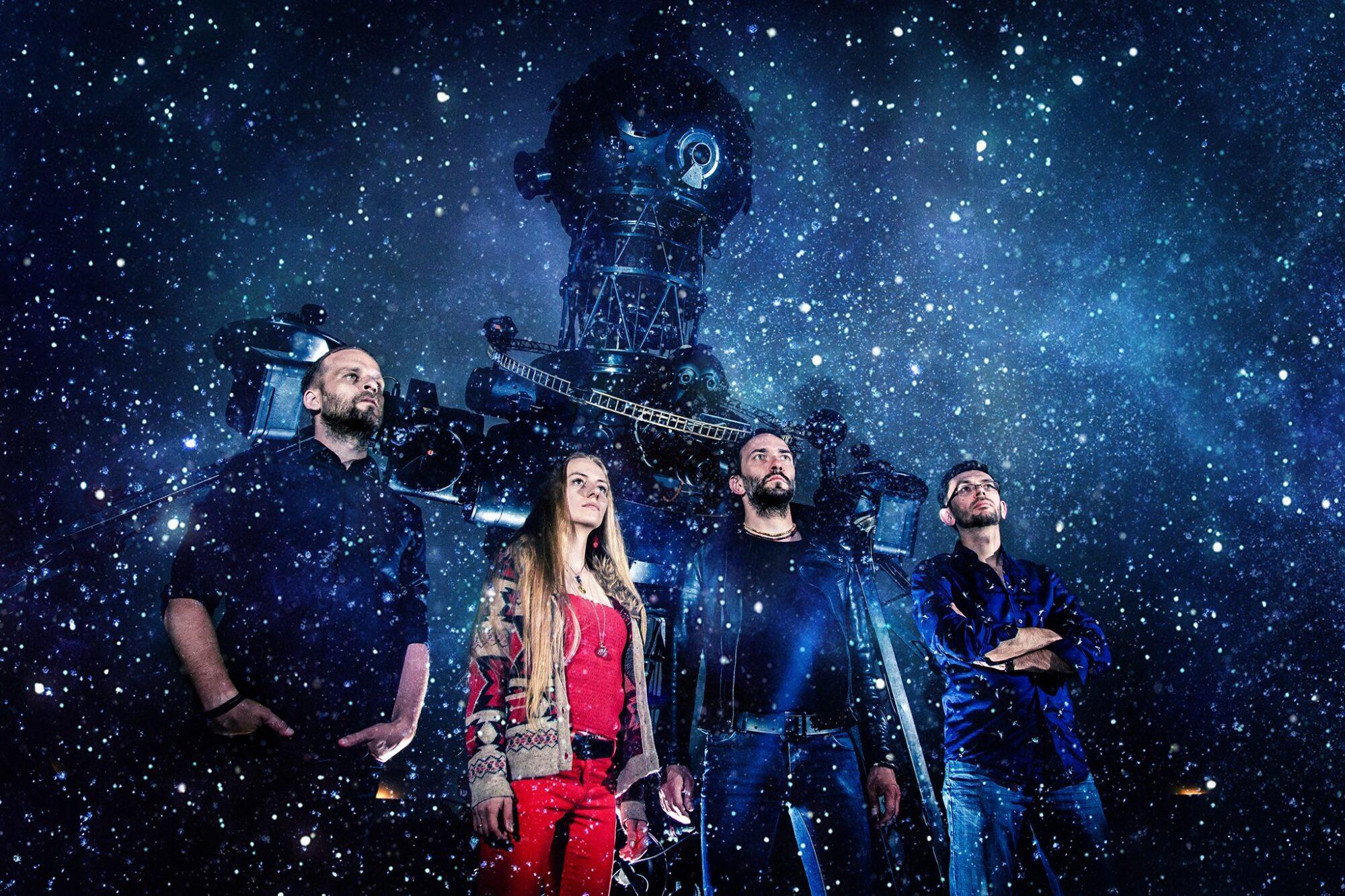 Cztery osoby stojące na tle urządzenia do wyświetlania mapy gwiazd w planetarium