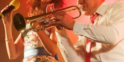 Na zdjęciu zespół HaNuta. Wokalistka w kolorowej sukience. Towarzysyz jej trębacz w białej koszuli i czerwonym krawacie.